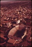 LINCOLN, THE CAPITAL CITY, SEEN FROM THE AIR. IN FOREGROUND IS THE UNIVERSITY OF NEBRASKA STADIUM - NARA - 547431