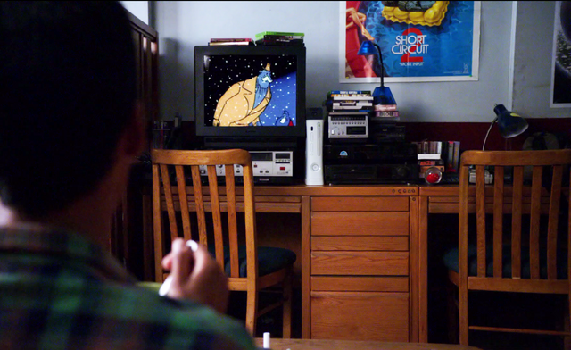 A bed's dorm room Abed watching TV