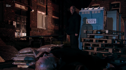 Phelan watches Michael as he dies