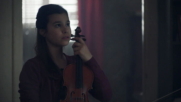 Alessandra-Reggiani-as-Young-Nadia-Feirro-with-violin-Counterpart-Starz-Season-1-Episode-2-Birds-of-a-Feather