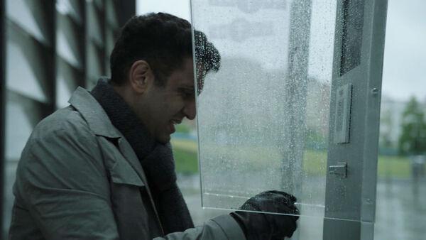 Adeel-Akhtar-Kasper-at-public-video-phone-Counterpart-STARZ-Season-1-Episode-9-No-Mans-Land