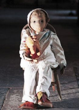 An old doll sat on a rocking chair with a teddy bear, he has creepy eyes and facial features.