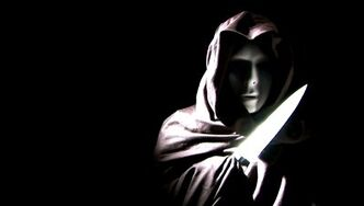 Stock-footage-a-person-masked-and-cloaked-in-black-flashing-a-knife