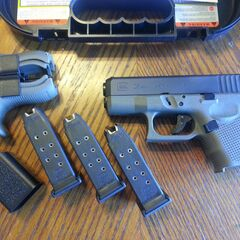 A Glock 26 with three magazines.