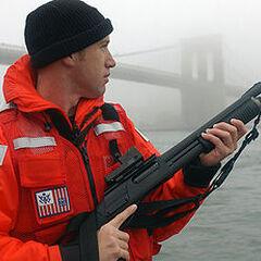 A U.S. Coast Guard member carrying a Remington Model 870.