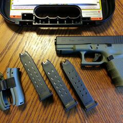 A battlefield green Glock 19 with several magazines and sights.