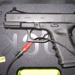 A Glock 19 in a case with a wire.