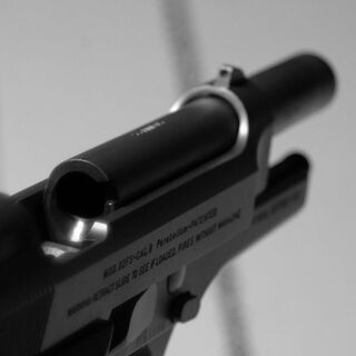 Detail of a Beretta 92FS ejection port and barrel.