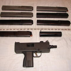 An unloaded MAC-10 with several magazines and a suppressor.
