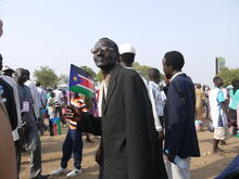 A South Sudanese man carries the flag (5925642623)