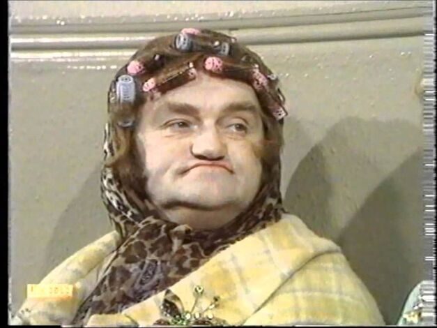 Les Dawson dressed as an old woman wearing curlers