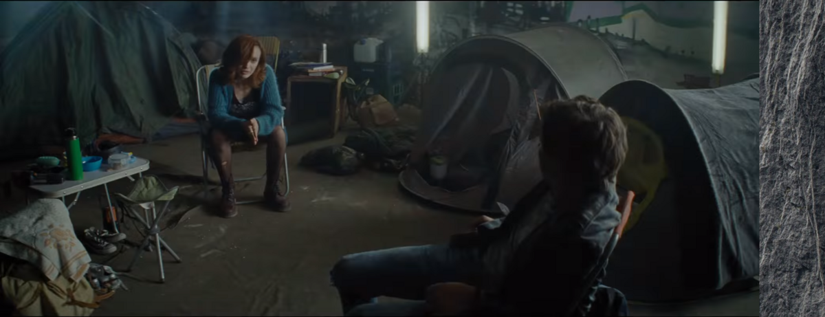 A scene from one of the trailers, with Samantha and Wade sitting in a dark room, filled with tents.
