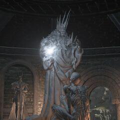 Posąg Gwyna i prawdopodobnie Sprytnego Karła w Mieście Pierścienia, w Dark Souls III