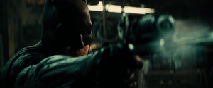 Batman fires a shot at a thug with his Grapple Gun
