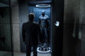 Bruce Wayne standing by the Batsuit.png