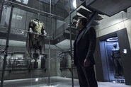 Bruce stares up at the damaged Robin Suit