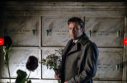 Bruce stands in the Wayne mausoleum