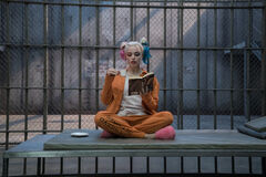 Harley Quinn holds tea and a book