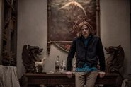 Lex Luthor leaning on a table - promotional still