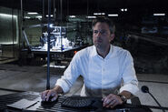Bruce Wayne sitting at his computer