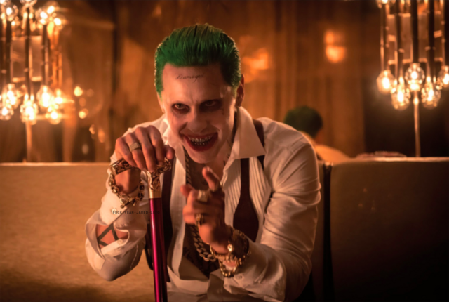 File:The Joker holds his cane and points.png