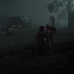 Victor y Barry desenterrando en el cementerio mientras Diana y Arthur observan.