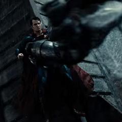 Batman aterriza encima de Superman.