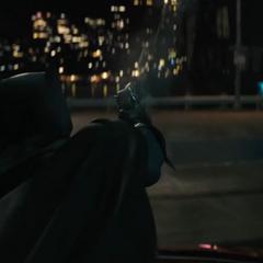 Batman usando su pistola de arpeo.