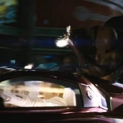 Batman recibiendo balazos en el techo del auto del Guasón.