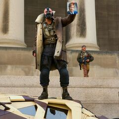 Bane holding up a photograph of Harvey Dent.