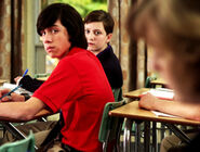 Eli & Adam In Their Degrassi Unifoms In A Degrassi Classroom Looking At Clare