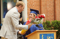 Mr. Simpson hands Holly J. flowers at graduation