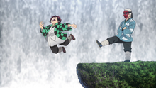 Urokodaki kicks Tanjiro into the water