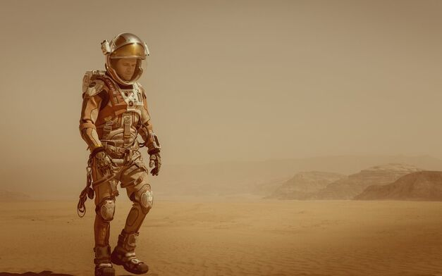 the martian matt damon in space suit walking across Mars sand