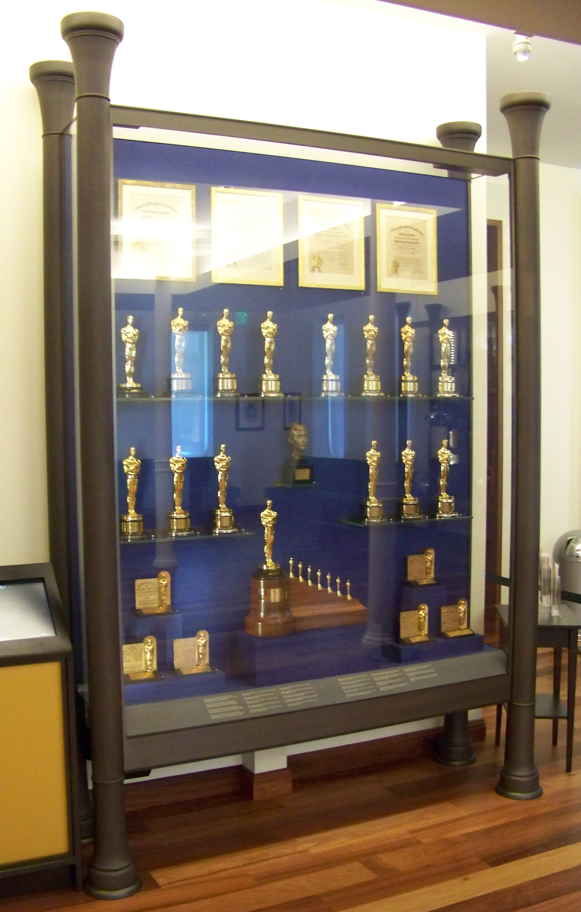 A Large Cabinet Containing Several Golden Statuettes And Few Certificates