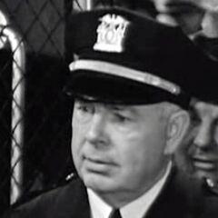 Capitán de policía Perie (William Halligan) en <a href=