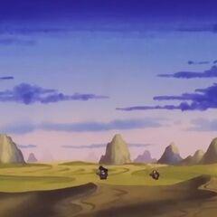 Goku e Crilin attraversano una zona desertica su Training Island durante il loro allenamento.