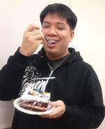James Hata eating 50th Booster Pack celebration cake