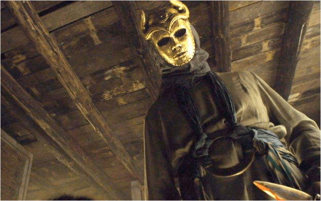 the son of the harpy Game of Thrones character wearing gold face mask