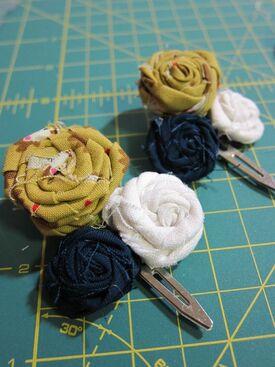 http://www.thezenofmaking.com/2011/06/fabric-rosette-barrette-tutorial