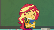 Sunset Shimmer smiling and hugging a yearbook EGFF