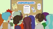Students around a bulletin board EG3