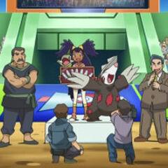 Iris como ganadora junto a sus Pokémon y con su premio.