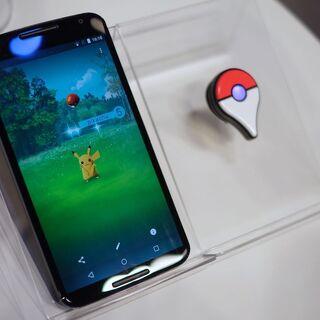 Foto de un <i>smartphone</i> con una versión beta de Pokémon GO y un Pokémon GO Plus.