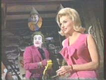 Queenie smirks as Joker shows of his utility belt (Nancy Kovack with Cesar Romero)