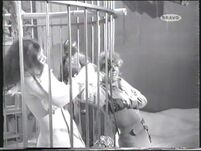 Mrs Peel pulling the panic striken receptionist through the bars (Yolande Turner with Diana Rigg)
