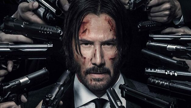 john wick keanu reeves with lots of people pointing guns at his head