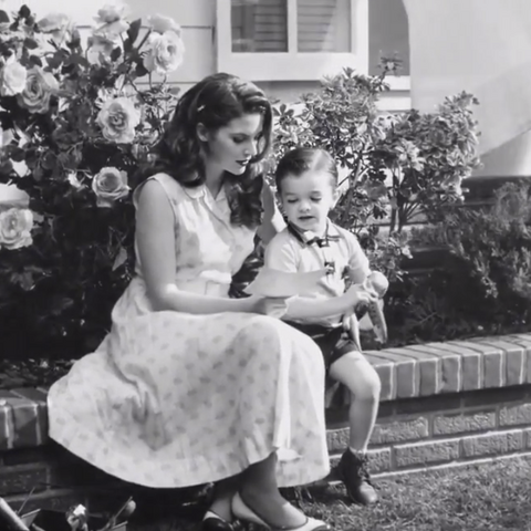 Його дружина і син, які розглядають його фотографію у <a href=