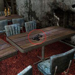 «10-мм пістолет НКР» на столі в їдальні.