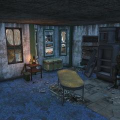 Кімната з ящиками, кріслами та кухнею.